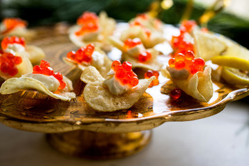 Close up of potato chips topped with caviar and lemon cream