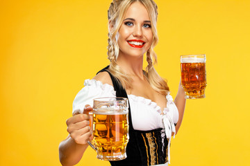Young sexy Oktoberfest girl waitress, wearing a traditional Bavarian or german dirndl, serving two big beer mugs with drink isolated on yellow background.