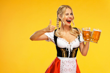Wow emotion. Young sexy Oktoberfest girl waitress, wearing a traditional Bavarian or german dirndl, serving big beer mugs with drink isolated on yellow background.