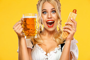 Young sexy Oktoberfest girl waitress, wearing a traditional Bavarian or german dirndl, serving big beer mugs with drink and french hot dog isolated on yellow background.