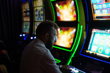 Man playing a slot machine in a casino