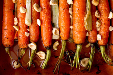 Close up of roasted carrots and scallions with thyme and hazelnuts