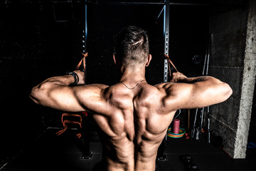 Young strong man workout training back muscles in the gym dark image