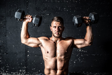 Young strong sweaty man shoulders workout training with two dumbbells in the gym dark image with shadows