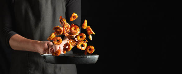 Professional chef prepares shrimps or langoustines with spices. Cooking mediterranean seafood, healthy vegetarian food on a dark background. With copy space for text