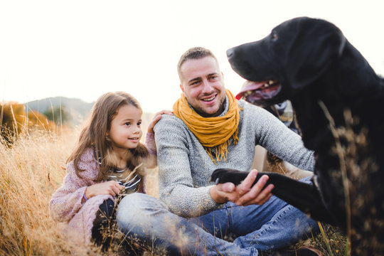 Father with small daughter and a dog sitting on grass in autumn nature.