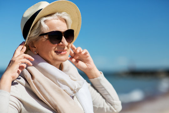people and leisure concept - portrait of happy senior woman in sunglasses and straw hat on beach in estonia