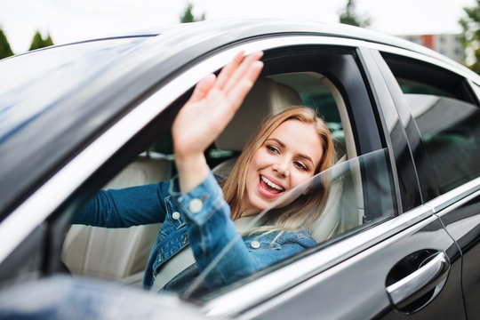Young woman driver sitting in car, greeting somebody.