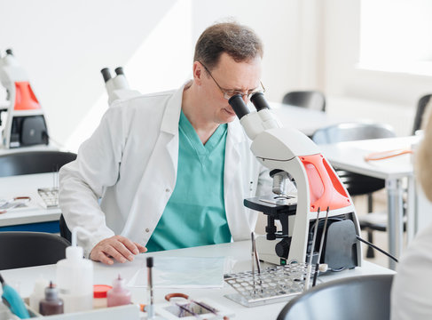 Senior researcher working with microscope in lab