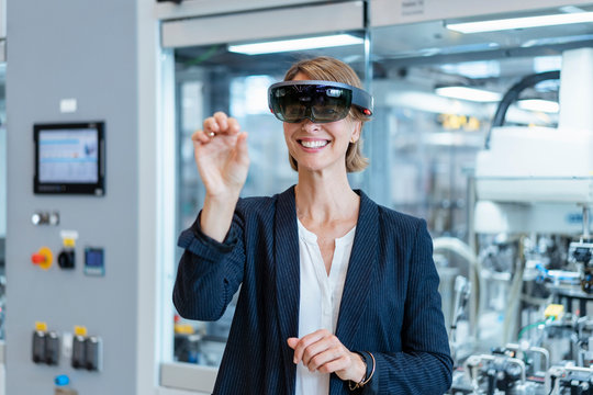 Smiling businesswoman wearing AR glasses in a modern factory