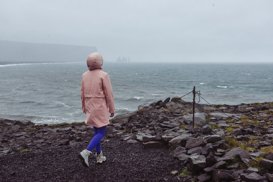 Icelandic black sand beach. Amazing lanscape nature in Iceland. Young traveller woman walking near the ocean view