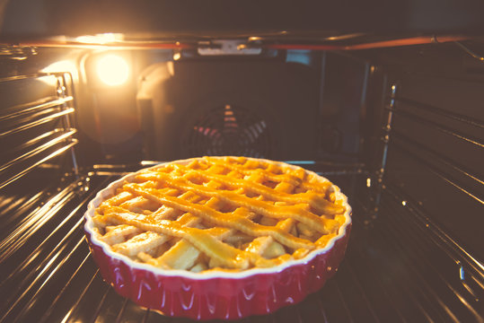 Fresh baked golden apple pie in red dish in oven at kitchen