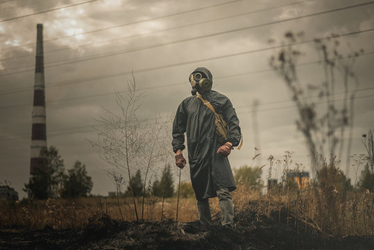 Man in gas mask and coat is walking on burnt ground on a smoking chimney background. Air pollution concept.