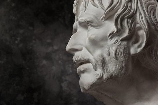 Gypsum copy of ancient statue Seneca head on dark textured background. Plaster sculpture man face.