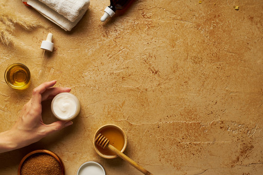 Spa beauty skincare flatlay on travertine background wiith female hand holding a  small container of cream. Overhead view, copy space