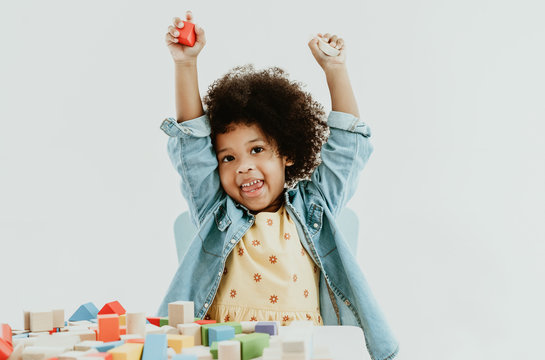 Cute little african american girl enjoy playing with colorful toy blocks on the table  at preschool.  Educational kids toy for nursery or kindergarten.