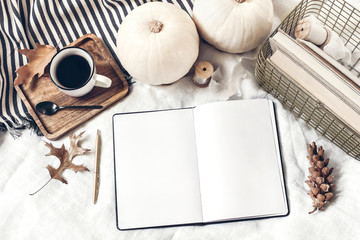 Autumn breakfast in bed composition. Blank open notepad, diary mockup. Cup of coffee, white pumpkins, plaid, oak leaves and old books. Linen background. Thanksgiving, Halloween. Flat lay. Top view.