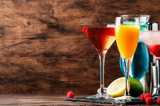 Colorful summer cocktails. Cold alcoholic beverages and drinks: mimosa, cosmopolitan, raspberry margarita and blue hawaii on wooden table background with bar tools