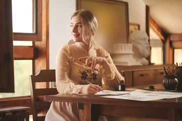 Creative young beautiful woman artist or poet sits at wooden table in art studio and writes  picture or letter in ink. Romantic stylish photo in warm beige colors