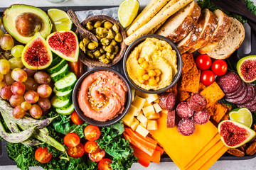 Meat and cheese appetizer platter. Sausage, cheese, hummus, vegetables, fruits and bread on black...