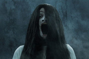 Scary ghost woman screaming on dark background