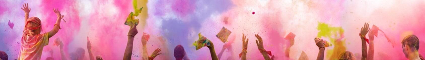 XXXL Breitbild - Holi Fest begeisterte Menschen jubeln auf einem Holifestival, tanzen und werfen mit buntem Holipulver