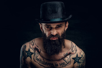 Portrait of strange funny man with hat, beard and a lot of tattooes at the dark background.