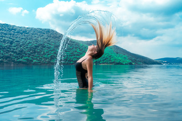 Beautiful girl splashing in the water. Colorful turquoise landscape. Rest, relax. Summertime. Vacation. Journey. In nature. Tropical. Enjoy life. Lifestyle. A young woman swimming in the lake. Island