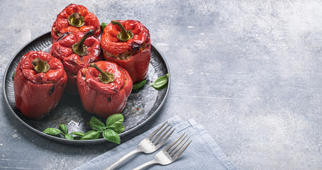 Stuffed red sweet peppers with meat and rice on metal tray with space for text