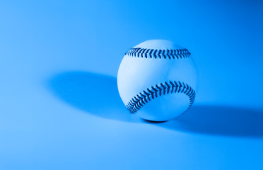 baseball on a blue color background and red stitching baseball. copy space