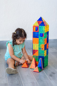 Little girl playing with lots of colorful plastic blocks constructor and builds house.