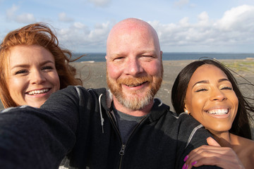 Bald man with two women at the beach