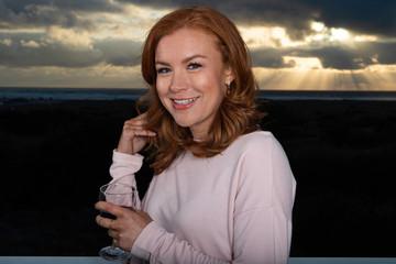 Portrait of redhead woman drinking wine outside