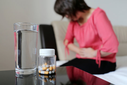 Stomach ache, bottle of pills and water glass on background of woman suffering from abdominal pain. Girl sitting on bed clutching her abdomen, concept of indigestion, menstruation