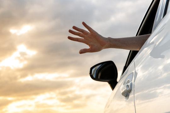 Man inside car showing his hand outdoor/leaning out of car window at sunset, relaxing, enjoying road trip and feeling the air and freedom.