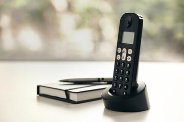 Telefono inalambrico y libreta con fondo verde fuera de foco y luz natural