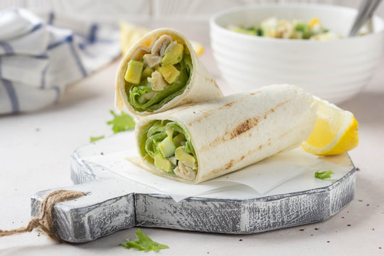 Grill roll of flatbread stuffed with avocado, cucumber, egg and white meat (chicken, squid, fish). Delicious lunch, snack, fast food, healthy food