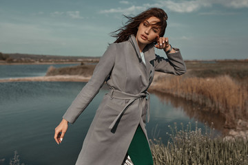 Beautiful elegant portrait of young woman in fashion grey coat outside. Sunny autumn ar spring weather. Wall mural