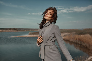Beautiful elegant portrait of young woman in fashion grey coat outside. Sunny autumn ar spring weather.