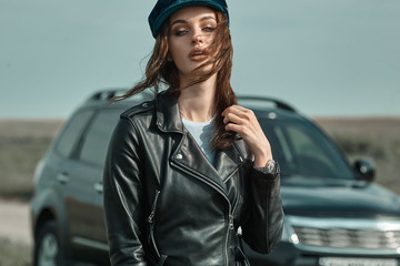 High fashion portrait of brunette woman outside in leather black jacket and trendy hat. Outdoor fashion.