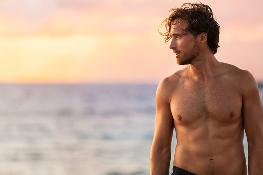 Beach body fit handsome man with six pack abs shirtless on summer Hawaii vacation sunset. Surfer lifestyle.