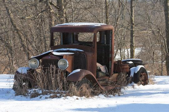 Old rusted car body in winter scene