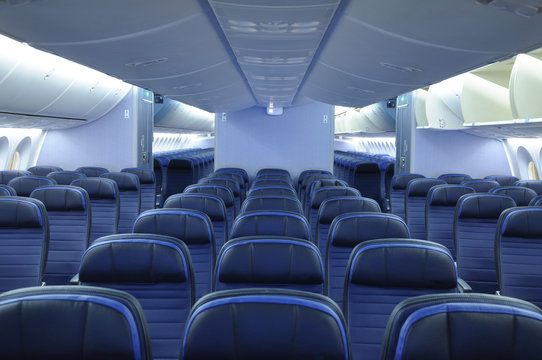 Empty commercial airplane cabin interior with blue leather seats. Two aisles and open overhead bins