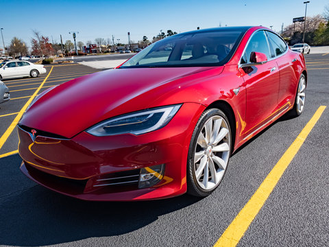 Red Tesla Model S Parked in Parking Lot Summer Day