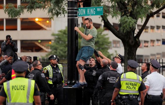 A man who climbed a traffic light to protest against lead in drinking water is assisted down by police officers outside the venue of the 2019 MTV Video Music Awards at the Prudential Center, Newark