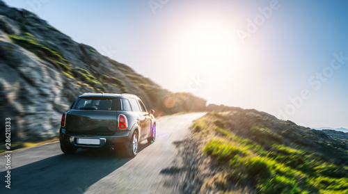 Wall mural rental car in spain mountain landscape road at sunset