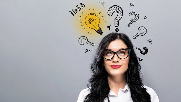 Idea light bulbs with question marks with young businesswoman in a thoughtful face