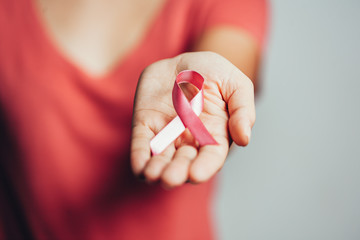 Healthcare and medicine concept - woman holding pink breast cancer awareness ribbon