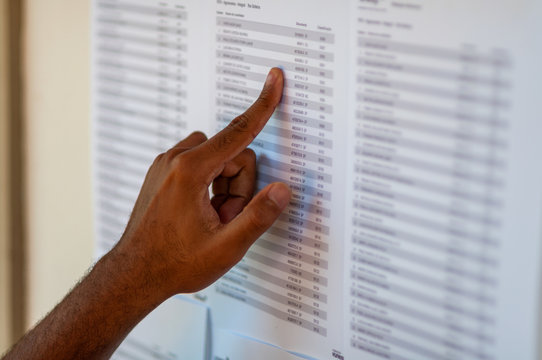 Man's hand pointing to a name list, trying to find some name