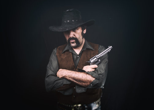 Cowboy standing with crossed arms, holding a revolver handgun.